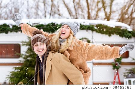 Happy winter couple having fun outdoors at campsite, guy piggybacking his girlfriend 69465563