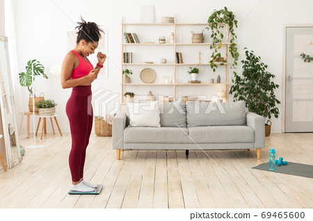 Joyful African American Girl Gesturing Yes Weighing On Scales Indoors 69465600
