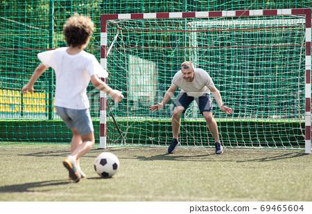 Little boy playing soccer, kicking ball to goal 69465604