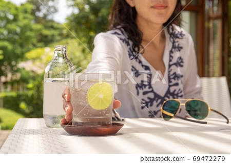 Woman hand reachinf glass of healthy nutrition of sparkling water. 69472279