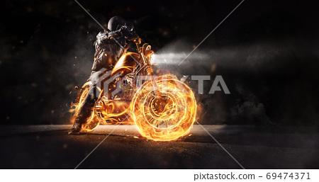 Dark motorbiker staying on burning motorcycle at night. 69474371