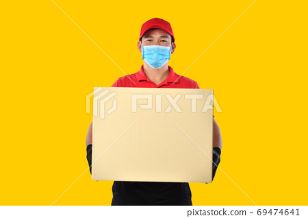 Asian delivery man in red uniform, medical face mask, protective gloves carry cardboard box in hand  69474641