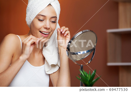 Portrait of beautiful woman cleaning teeth with dental floss 69477530