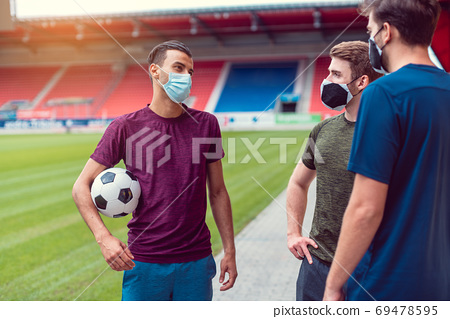 Soccer players in football stadium during covid-19 wearing masks 69478595
