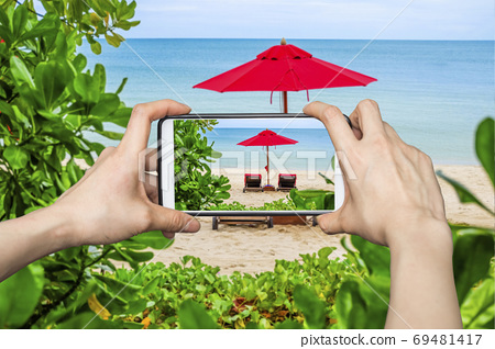 Woman Taking pictures on mobile smart phone show Red Umbrella on 69481417