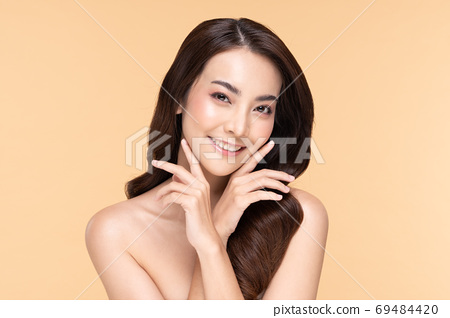 Beautiful Asian young woman touching soft cheek smile with clean fresh skin Happiness and cheerful with positive emotional,isolated on Beige background,Beauty Cosmetics and Facial treatment Concept 69484420