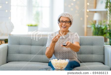Senior woman watching TV 69486813