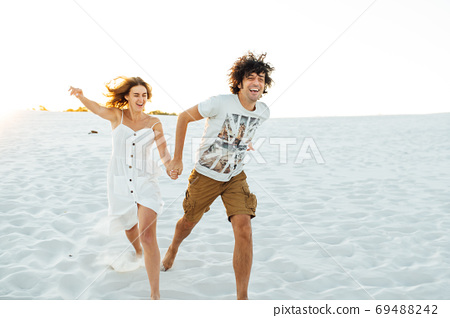 Cheerful couple in love running on the beach and enjoying their vacation 69488242