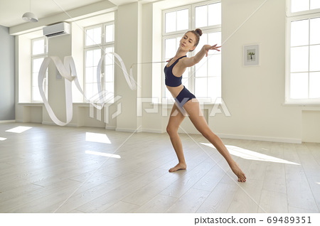 Young gymnast in black clothes with a ribbon performs an element of rhythmic gymnastics in the gym 69489351