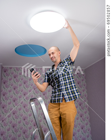 A man installs a smart led ceiling light and connects to it using an app on his smartphone. 69502857