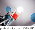 The woman in the room sets the led ceiling light. 69502905