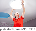 Installing a ceiling light in the children's room. Woman sets the ceiling lamp on the ceiling. 69502911