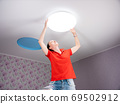 A woman in a children's room sets a ceiling lamp. 69502912