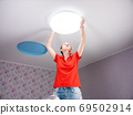 The woman in the room sets the led ceiling light. 69502914