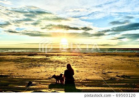 一個女人一邊看日落一邊walking狗 69503120