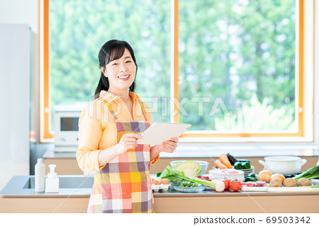Middle woman using a tablet in the kitchen 69503342