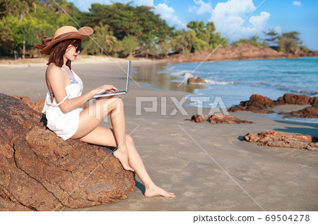 beautiful and cute businesswoman using computer and cell phone with sun glasses and hat on the beach 69504278