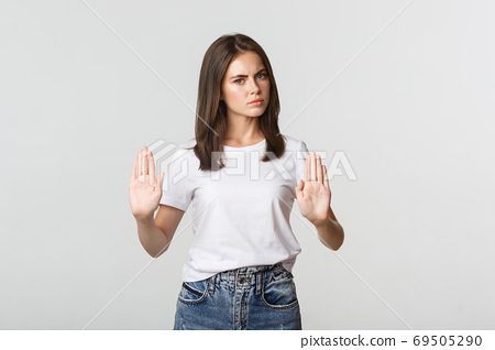 Serious displeased young woman showing stop gesture, saying no 69505290