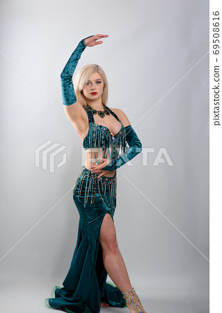 Young beautiful exotic eastern women performs belly dance in ethnic green dress. 69508616