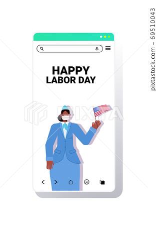 stewardess in uniform holding USA flag labor day celebration concept woman wearing mask to prevent coronavirus 69510043