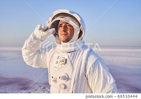 Spaceman with opened helmet looking forward 69510444