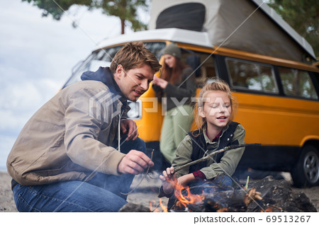 Daddy and daughter fan the fire at the nature 69513267