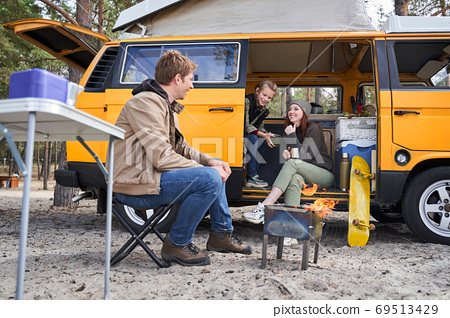 Family enjoying picnic near campfire 69513429