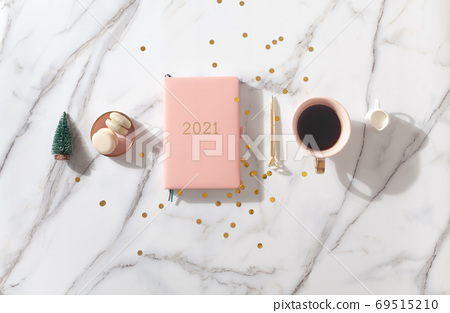 Flat lay composition with New Year's decoration, coral colored 2021 diary book and coffee cup and Macaron cookie 69515210