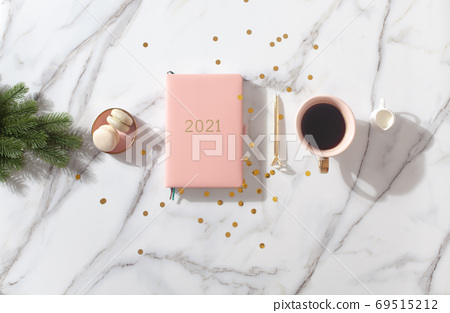 Flat lay composition with New Year's decoration, coral colored 2021 diary book and coffee cup and Macaron cookie 69515212