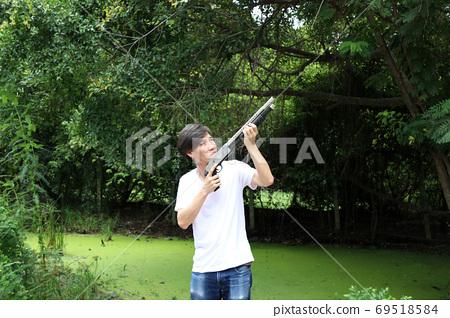 The gunner man standing long gun aiming top left sideways with w 69518584