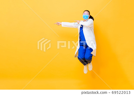Asian female doctor with medical mask jumping and pointing  69522013