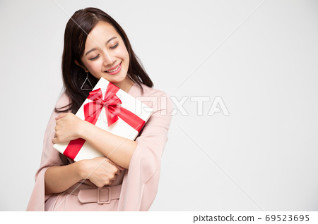 Happy beautiful asian woman smile and hugging gift box. 69523695