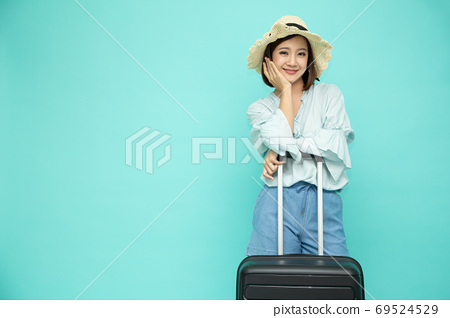 Asian woman with suitcase isolated on green background. 69524529