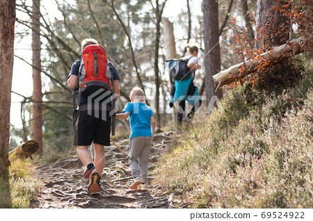 Rear view of unrecognizable young active family hiking together on mountain forest trackin in fall. Parents wearing backpacks and child toys. 69524922