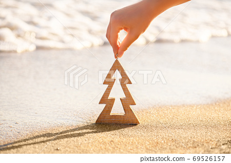 Female hand holding wooden Christmas tree on a sand on a beach near ocean, summer Christmas and winter holyday concept 69526157
