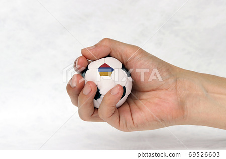 Mini football in hand and one black point of football is Armenia flag on white background. 69526603