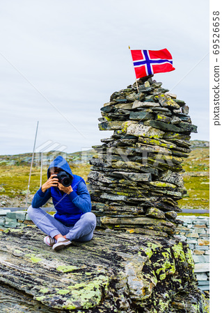 Tourist with camera in Norway mountains 69526658