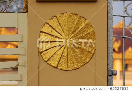 Gold stucco circle on the fence, symbolic of Dharma wheel. 69527655