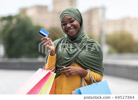Black Musim Woman Posing With Colorful Shopping Bags And Credit Card Outdoors 69527864