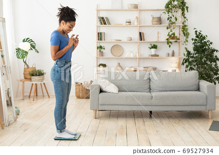 African American Girl Standing On Weight Scales After Dieting Indoor 69527934