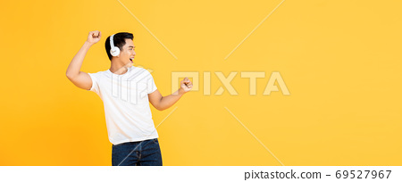 Asian man wearing headphones listening to music and dancing 69527967
