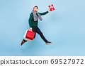 Asian man in Christmas attire jumping with red shopping bag and gift box 69527972