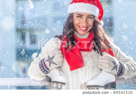 Woman in a red Christmas hat and scarf, white sweater and gloves 69542310