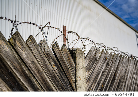 A wooden fence with barbed wire on top against the backdrop of a 69544791