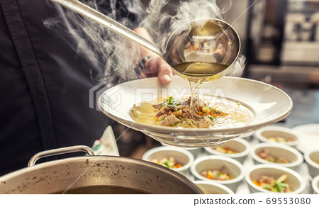 Chef pours broth into a chicken soup with noodles, meat and vegetable 69553080