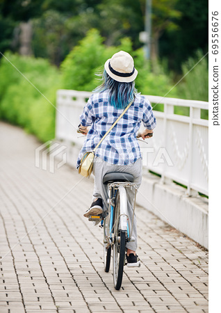 Woman riding on bicycle 69556676