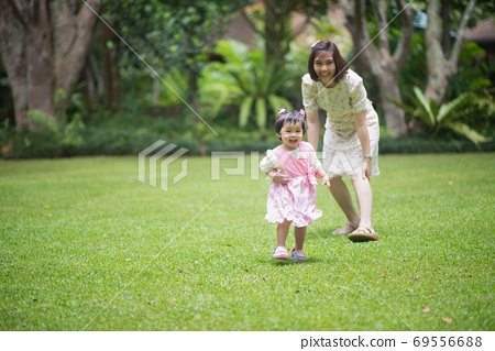 cute baby playing with mother in the garden 69556688