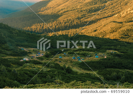 Sunrise in the Carpathians, on the Montenegrin saddle can be seen on the horizon tent camp, tents in the mountains, camping in the Carpathians. 69559010