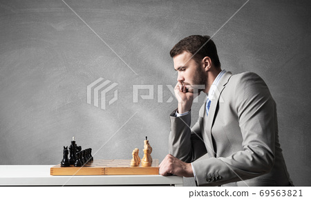 Businessman moving chess figure in chessboard 69563821