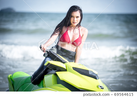 Asian female in bikini sitting on jet ski. 69564615